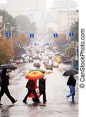 urban people cross the street in the rain