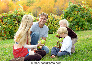 Family Eating Apples at Orchard in Autumn - a young,...