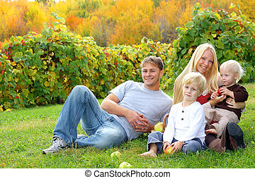 Happy Family Sitting in the Grass Eating Apples at Orchard -...