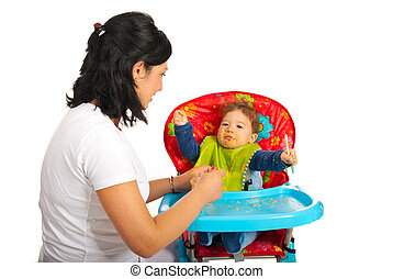 Mother feeding baby with puree