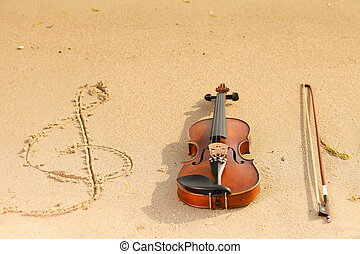 Violin and g clef on beach Music concept - Violin string and...