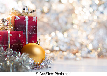 Christmas ball and gifts on abstract light background.