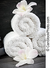 White rolled up spa towels with orchids flowers