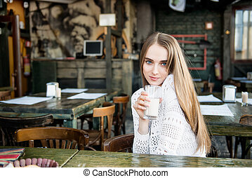 Beautiful happy woman drinking at the cafe