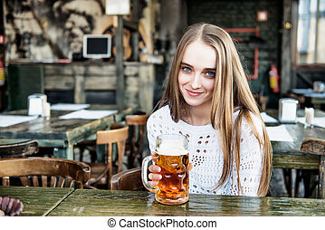 Beautiful woman drinking beer at the cafe