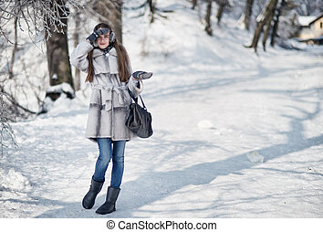 Beautiful happy woman walking in the winter forest