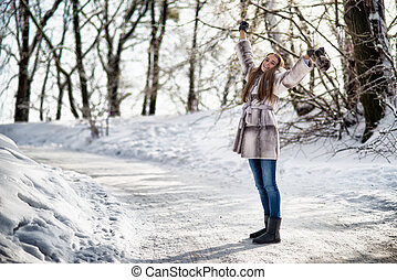 Beautiful woman walking in winter forest and have fun