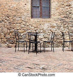 Old outdoor cafe in a traditional tuscany street - Italy