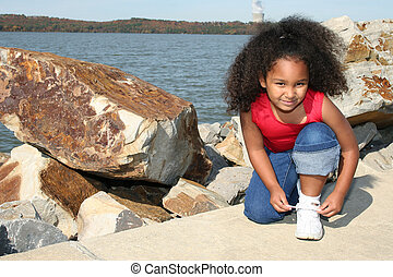 shoe - Adorable five year old African American Girl tying...