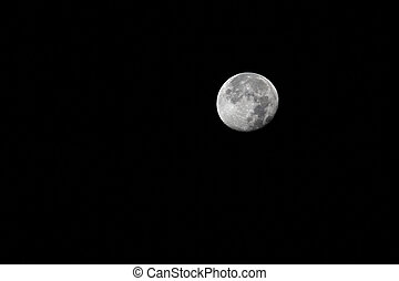 Full moon with relief spots on the black sky.