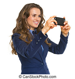 Smiling business woman taking photo using cell phone