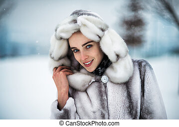 Portrait of beautiful smiling woman in fur coat in the park