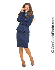 Full length portrait of smiling business woman talking mobile phone