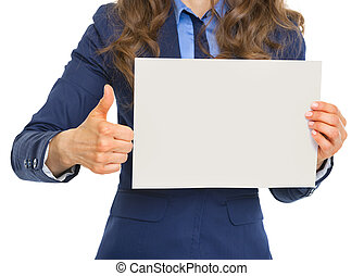 Closeup on business woman showing blank paper sheet and thumbs up