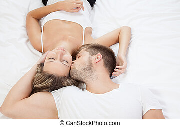 Young romantic couple in bed - Young romantic couple lying...