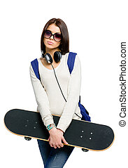 Portrait of teenager with skateboard, headphones and...