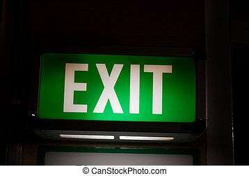 Exit sign glowing green in the dark