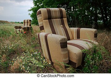 Armchairs - Two discarded armchairs on a field