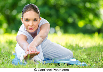 Portrait of sportive woman stretching in park - Portrait of...