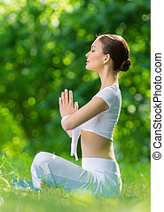 Profile of woman in lotus position prayer gesturing -...