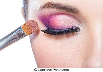 Close up of girl applying bright makeup - Close up of brush...