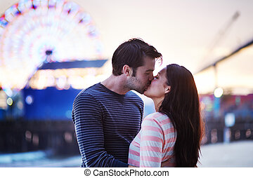 young couple kissing near santa monica pier