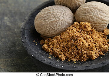 nutmeg whole and grated in a wooden bowl