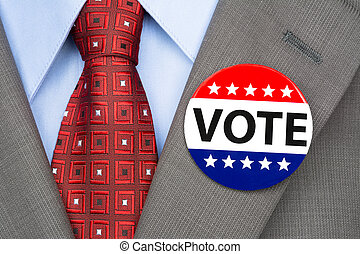 Vote pin on brown suit - A voter wears a vote pin on his...