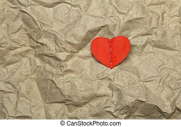 red heart on crumpled paper background