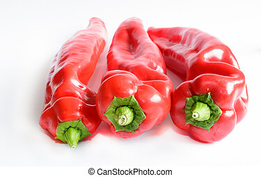 Three red peppers on white