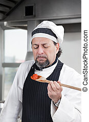 chef - mature chef holding wooden spool and tasting tomato...
