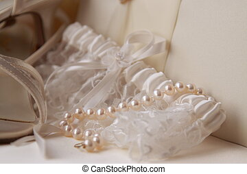 Garter and Pearls - A close-up of a white garter and pearls