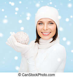 woman in hat, scarf and gloves with christmas ball