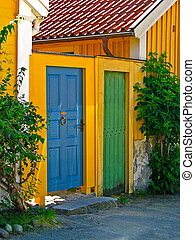 Two doors - Yellow buildings with one blue and one green...
