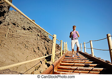 man trekking on wooden stairs along a rocky path