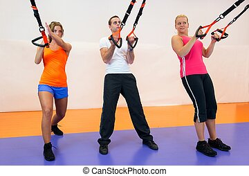 Young woman doing suspension training at the health club