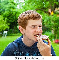 boy eating a bread - boy eating in the garden