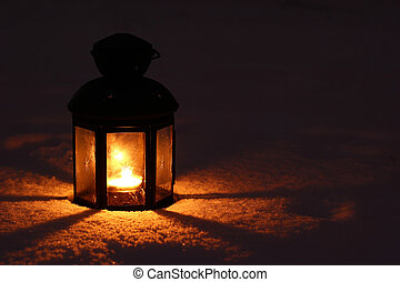 Candle lamp in snow at night