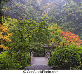 Foggy Morning in Japanese Garden with Wooden Foot Bridge...