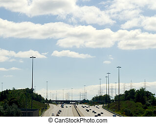 Highway under partly cloudy sky - Wide multi-lane highway...