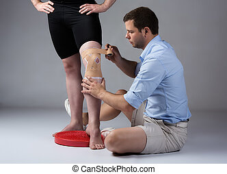 Adult male physiotherapist strapping the knee of a male...