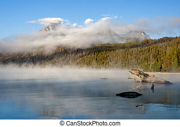 Fog floats around the mountain peaks with a lake