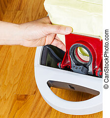 Replacing Vacuum Cleaner Bag - Vertical photo of female hand...
