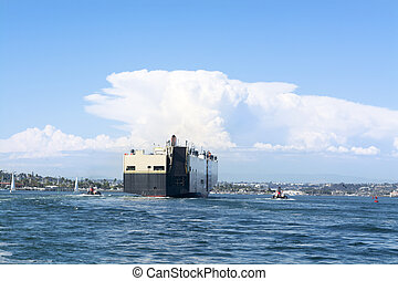 Freighter guided by tugboats - A large commercial tanker...