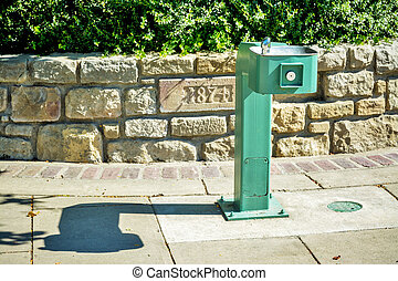 water fountain in a park with sandstone wall - Sunny hot day...