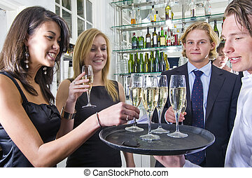 serving champagne - a waiter serving glasses of champagne on...
