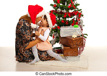 Mother kissing daughter near Xmas tree - Mother kissing her...