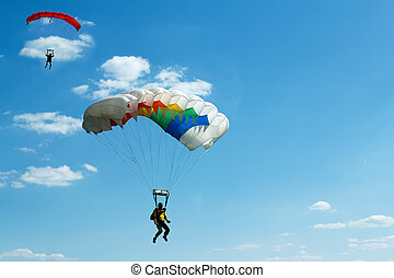 unidentified skydivers on blue sky - two silhouettes of...