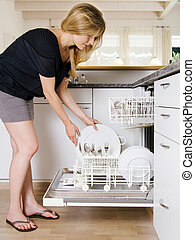 Female emptying the dishwasher - Photo of a blond female...