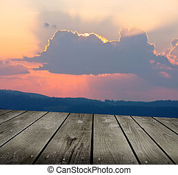 Sunrise in the mountains and empty wooden deck table. Ready...